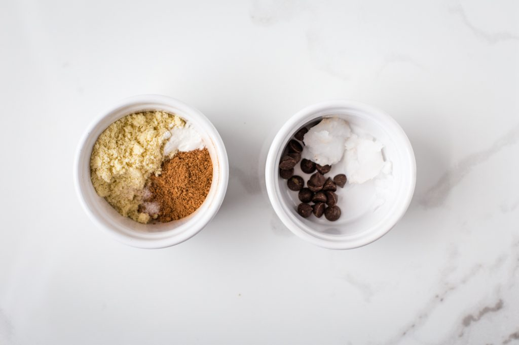 Dry ingredients in white ramekin on left, and coconut oil and chocolate chips in white ramekin on the right