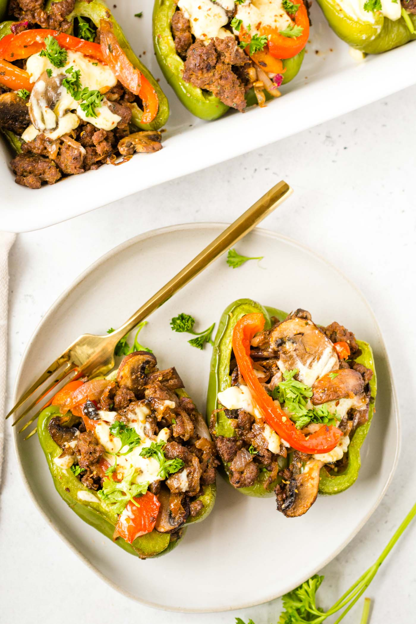 Two green philly stuffed peppers on plate with gold fork