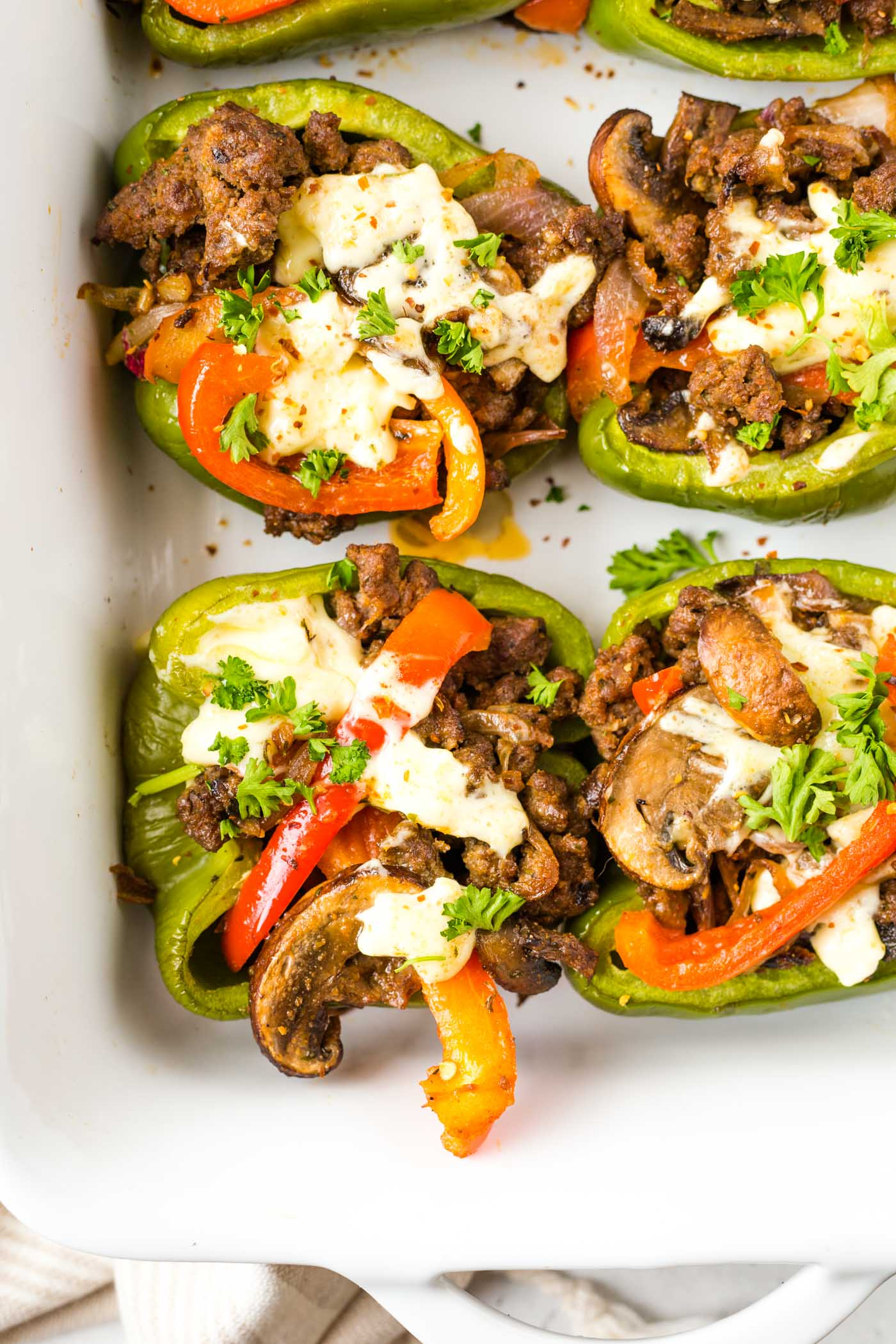 Halved green bell peppers stuffed with ground beef, red bell peppers, onion, and mushrooms