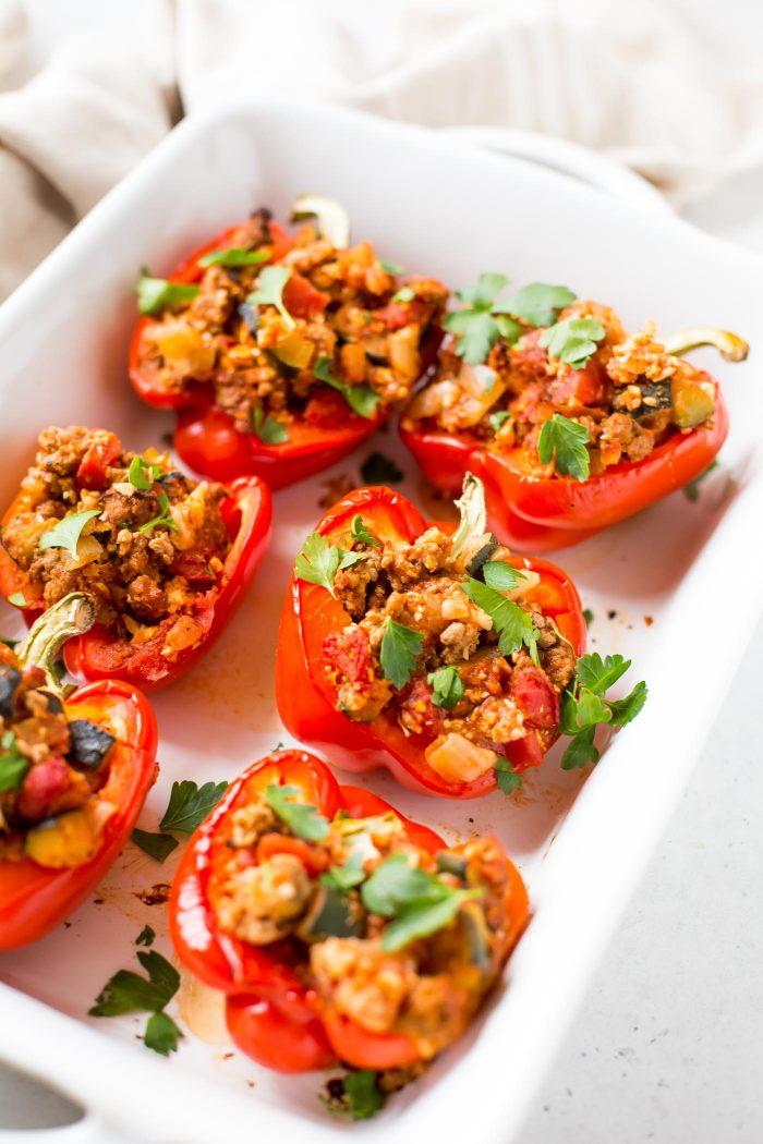 Italian stuffed red bell peppers in casserole dish