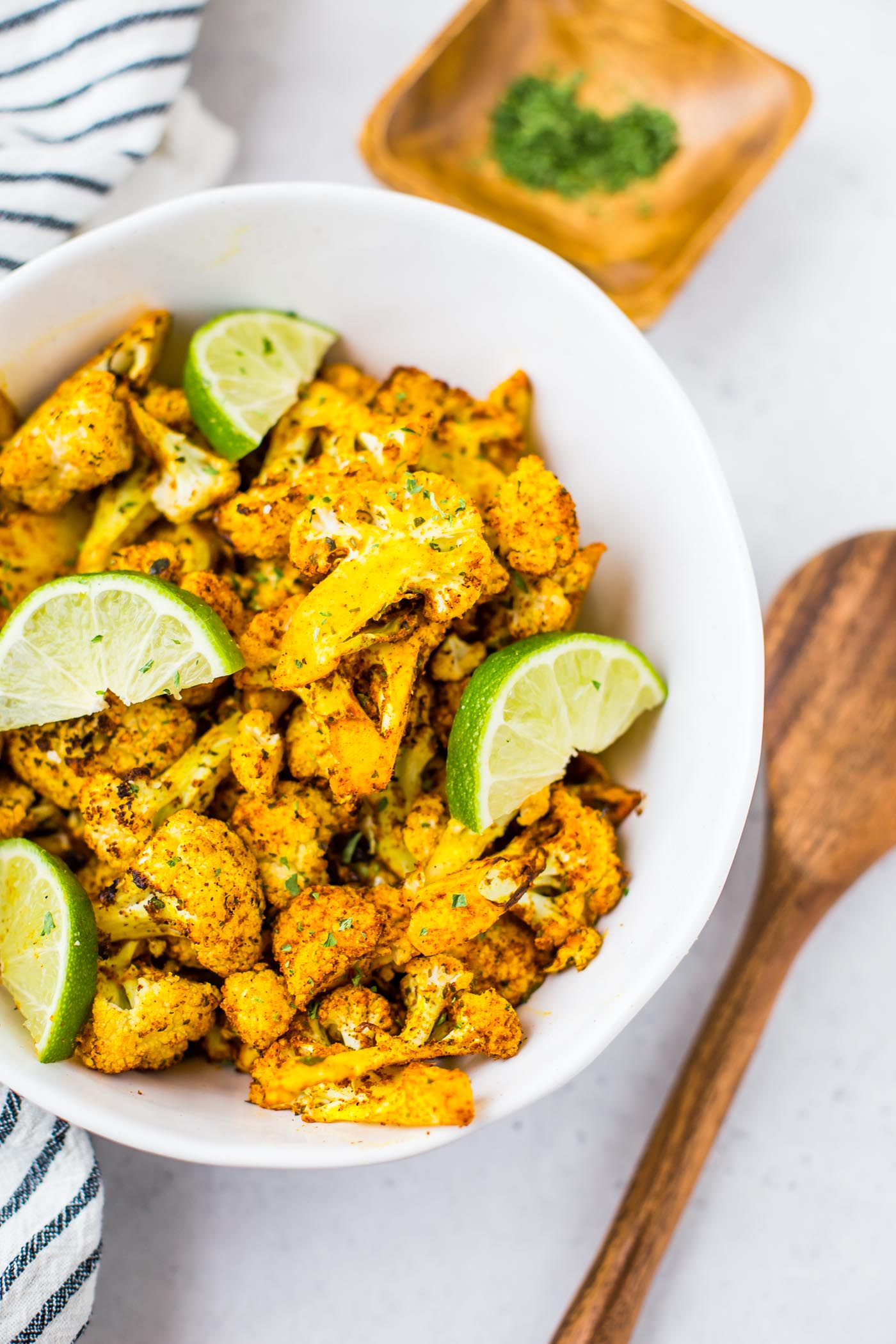 Mexican Cauliflower air fryer in white bowl topped with sliced limes
