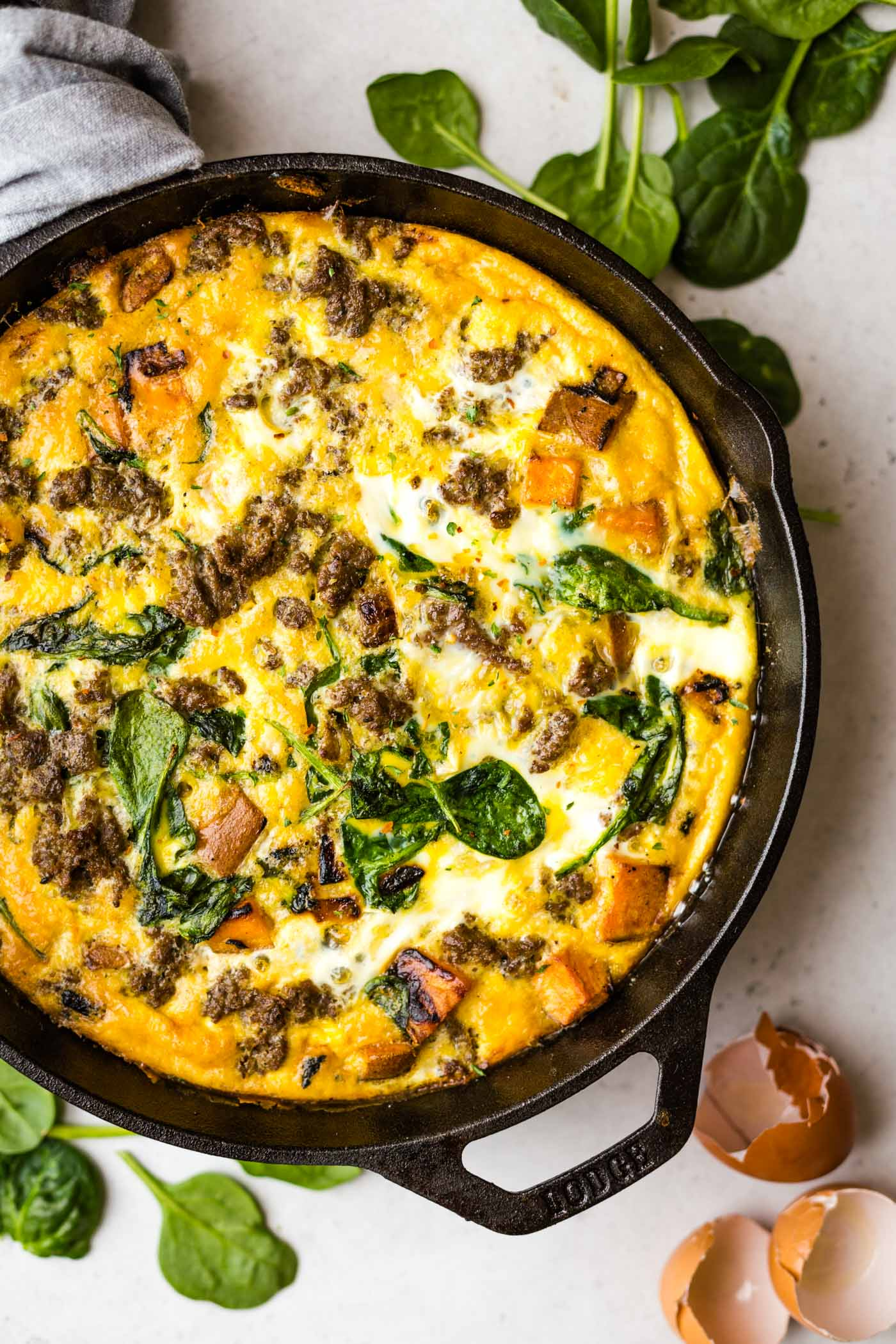 Paleo Sweet Potato and Sausage Frittata in cast iron skillet with cracked eggs and spinach and the background