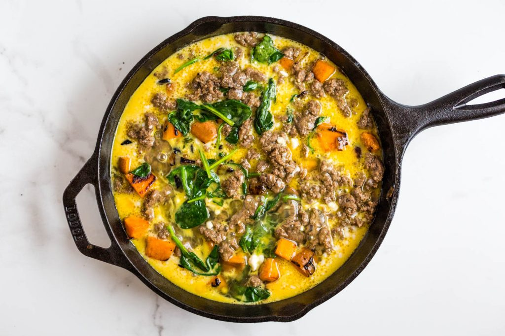 Raw egg, cubed sweet potato, breakfast sausage and spinach in cast iron skillet