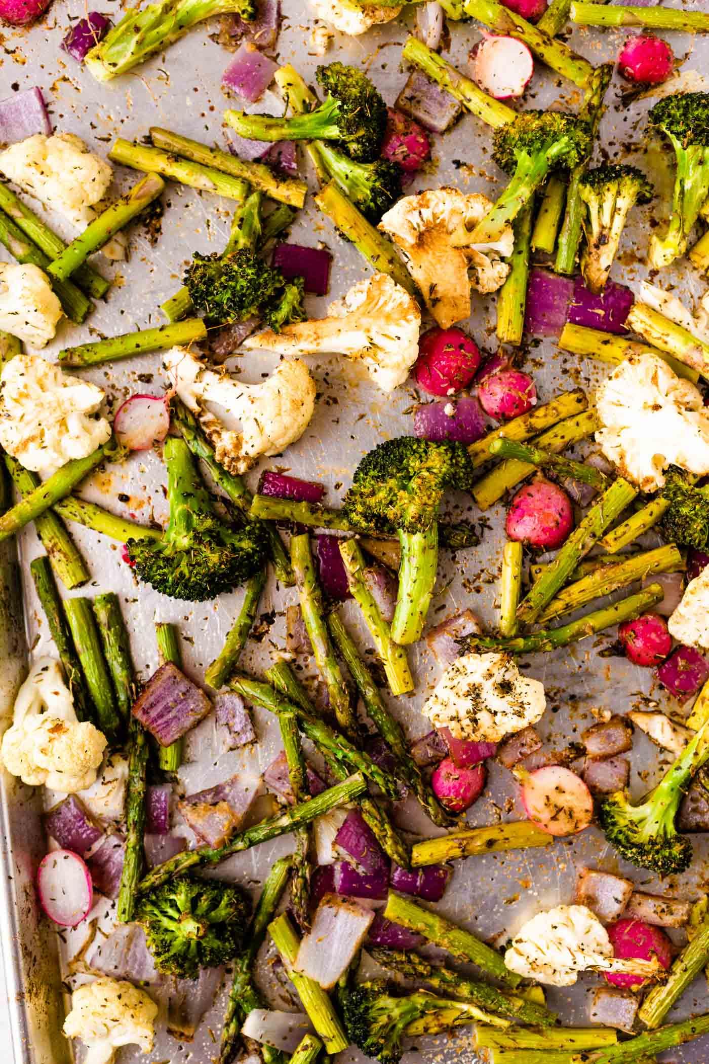 Roasted broccoli, asparagus, cauliflower, radishes and red onion on baking sheet