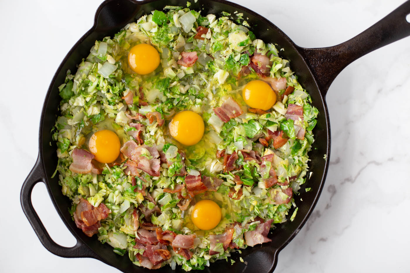 Shredded brussels sprouts, cooked bacon, and raw eggs in cast iron skillet
