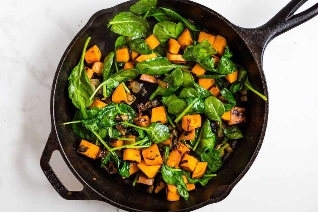 Sweet Potatoes, spinach, onions, and garlic in cast iron skillet