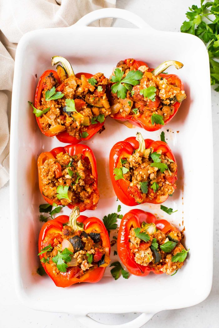 Whole30 Italian stuffed red bell peppers garnished with italian parsley in white casserole dish