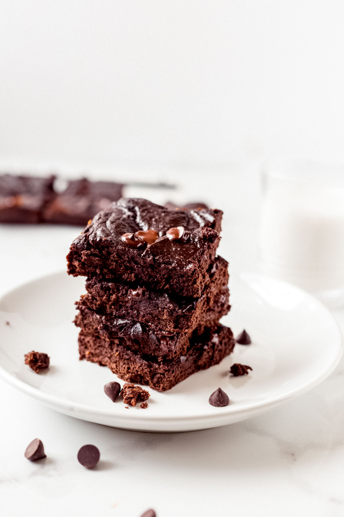 brownies stacked on a white plate with glass of milk and brownies behind on white background
