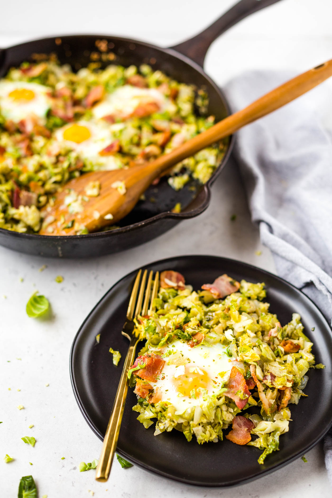 Brussels sprouts, bacon, and egg hash on a black plate with a gold fork
