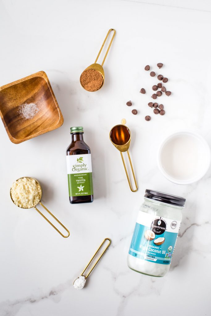 Ingredients to gooey brownie in a mug: chocolate chips, coconut oil, baking powder, almond flour, sea salt, cacoa powder, and maple syrup on white background
