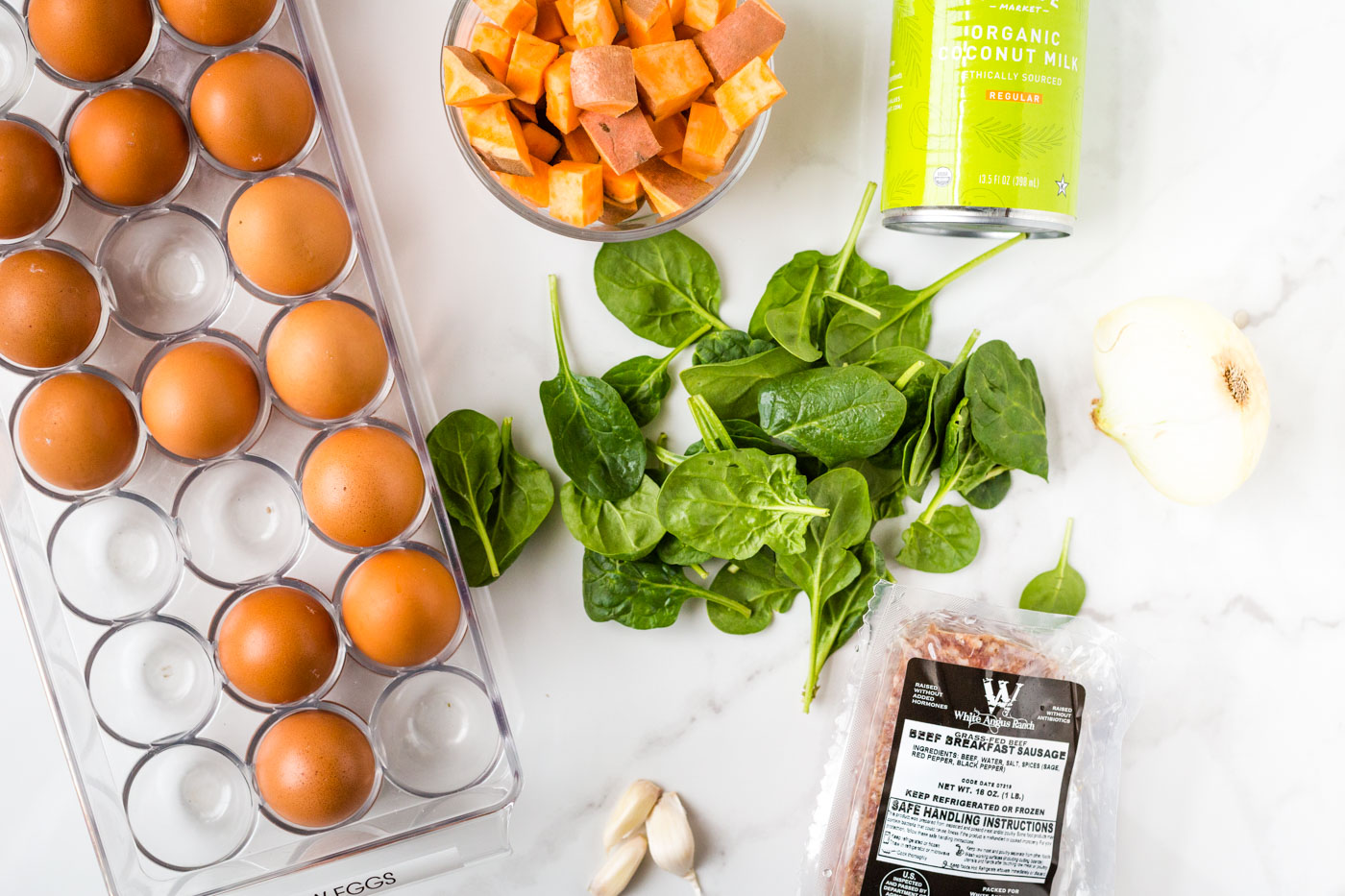 eggs, cubed sweet potato, spinach, breakfast sausage, half an onion, garlic cloves, and coconut milk on white background
