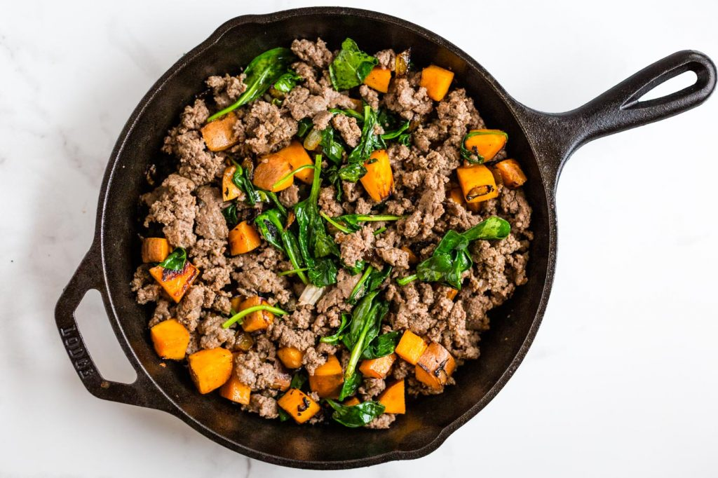 spinach, breakfast sausage, and sweet potato in cast iron skillet