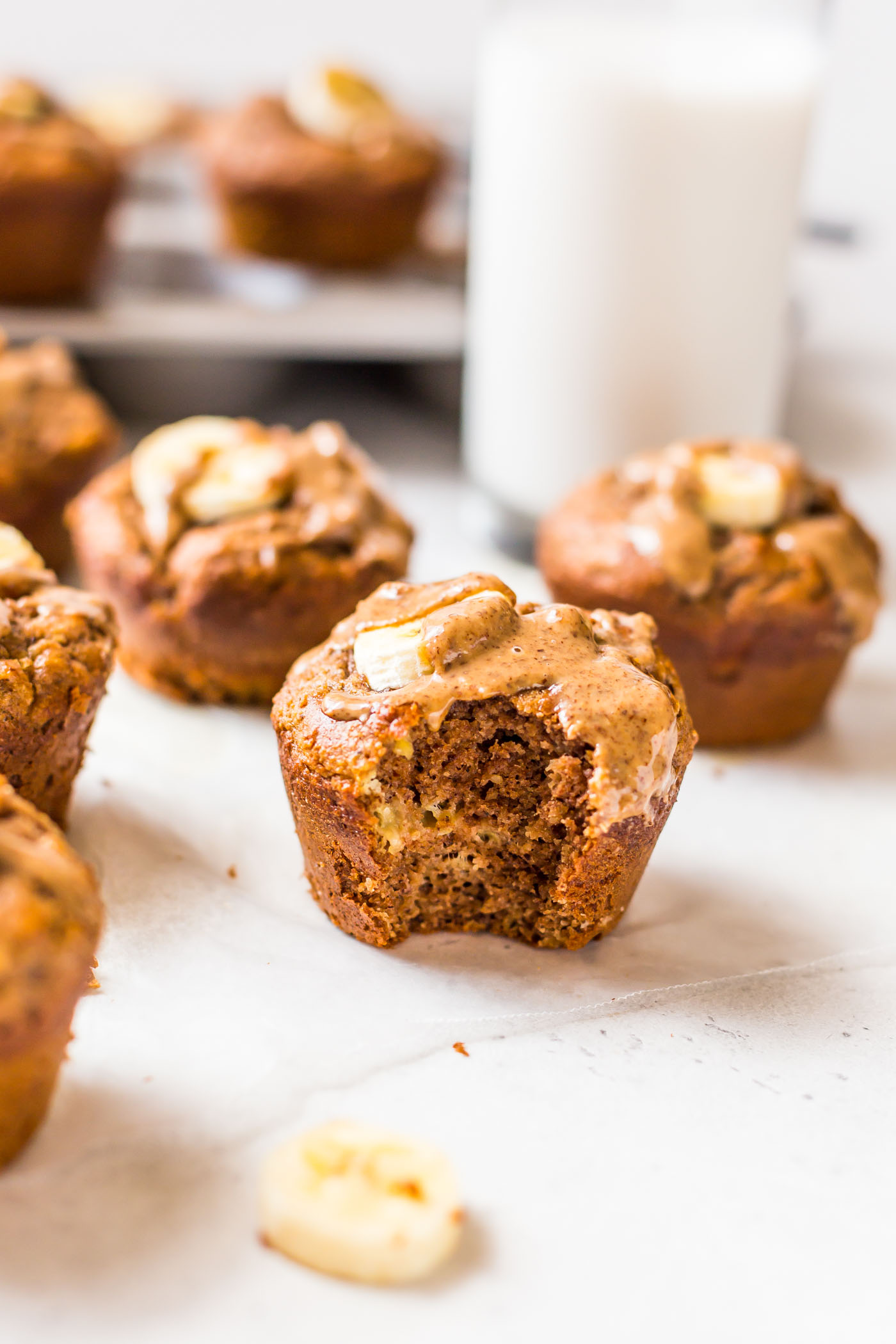 Baked Banana Protein Muffin with a bite bitten out of it on a white background