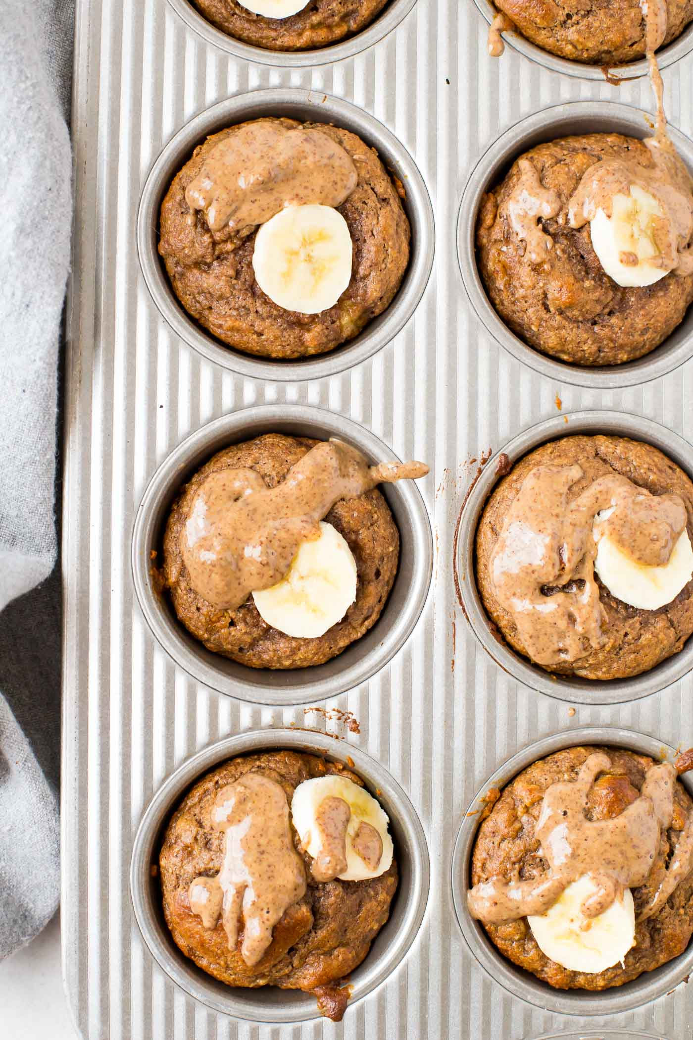 Banana Protein Muffins drizzled with almond butter in muffin tin pan