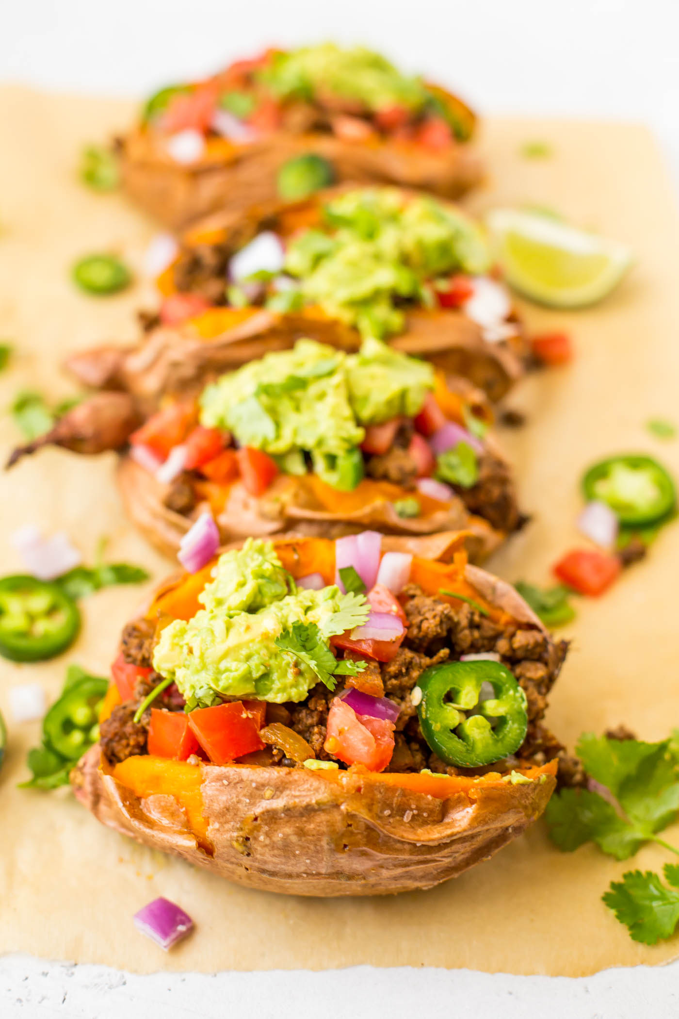 Four sweet potatoes stuffed with mexican ingredients ground beef, jalepenos, diced tomatoes, diced onion, cilantro, and smashed avocado