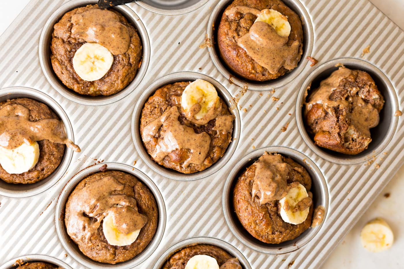 Protein Powder Muffins topped with banana slices and almond butter in muffin tin pan