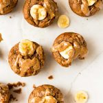 Protein muffins topped with a slice of banana and drizzled with almond butter on white background