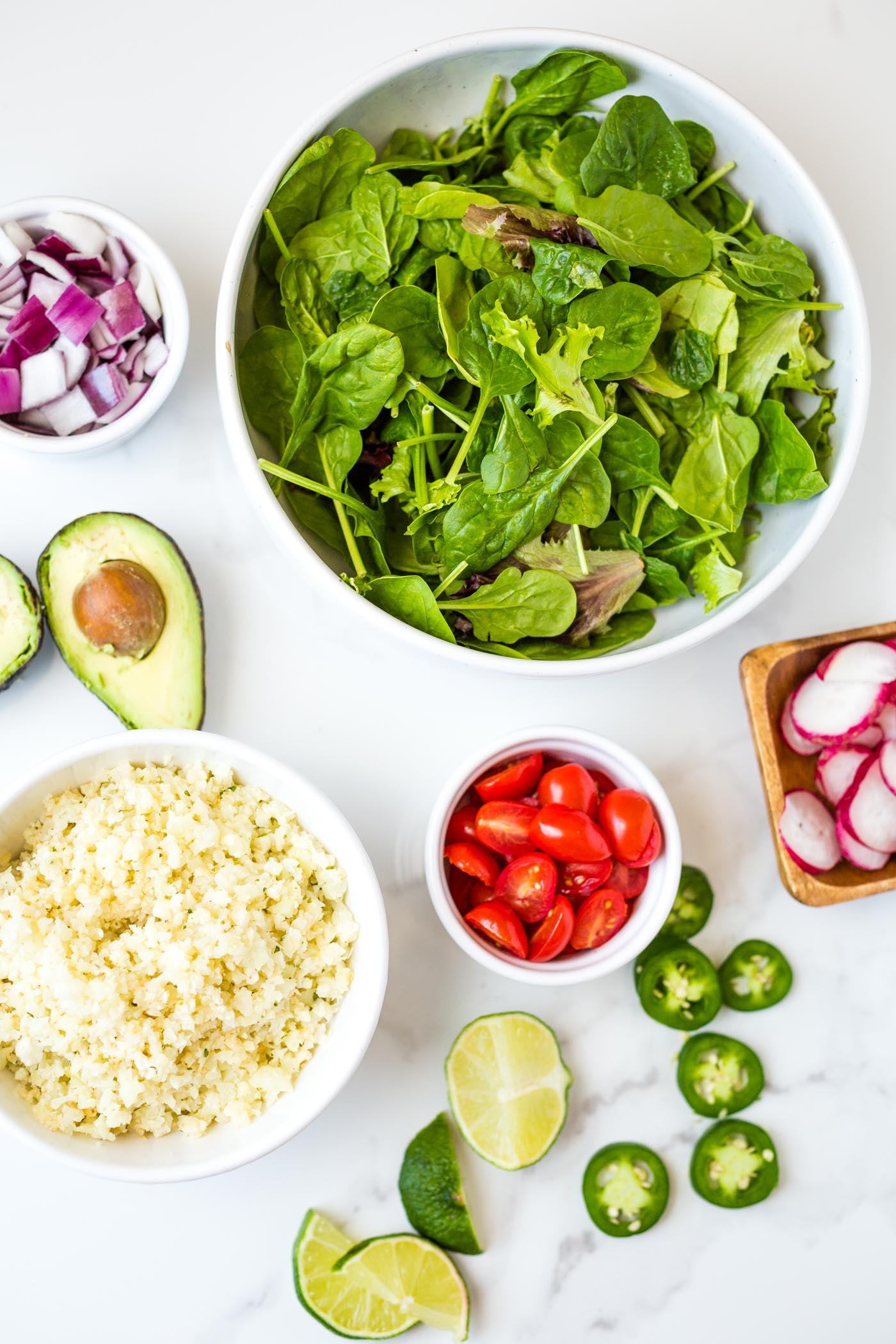 toppings including red onion, halved tomatoes, jalapenos, cauliflower rice, mixed greens, radishes, limes and halved avocados on white background