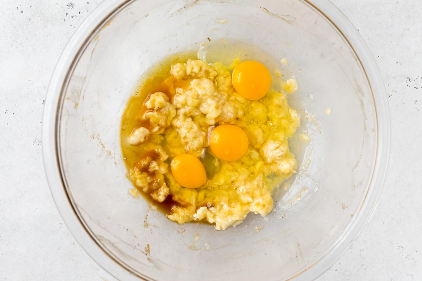 Smashed banana, whole eggs, honey, and vanilla in glass mixing bowl