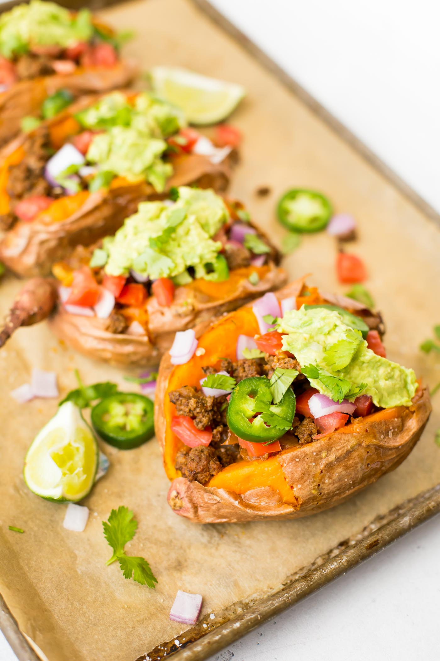 Stuffed Sweet Potatoes with ground beef, jalapenos, smashed avocado, diced tomato and onion on baking sheet