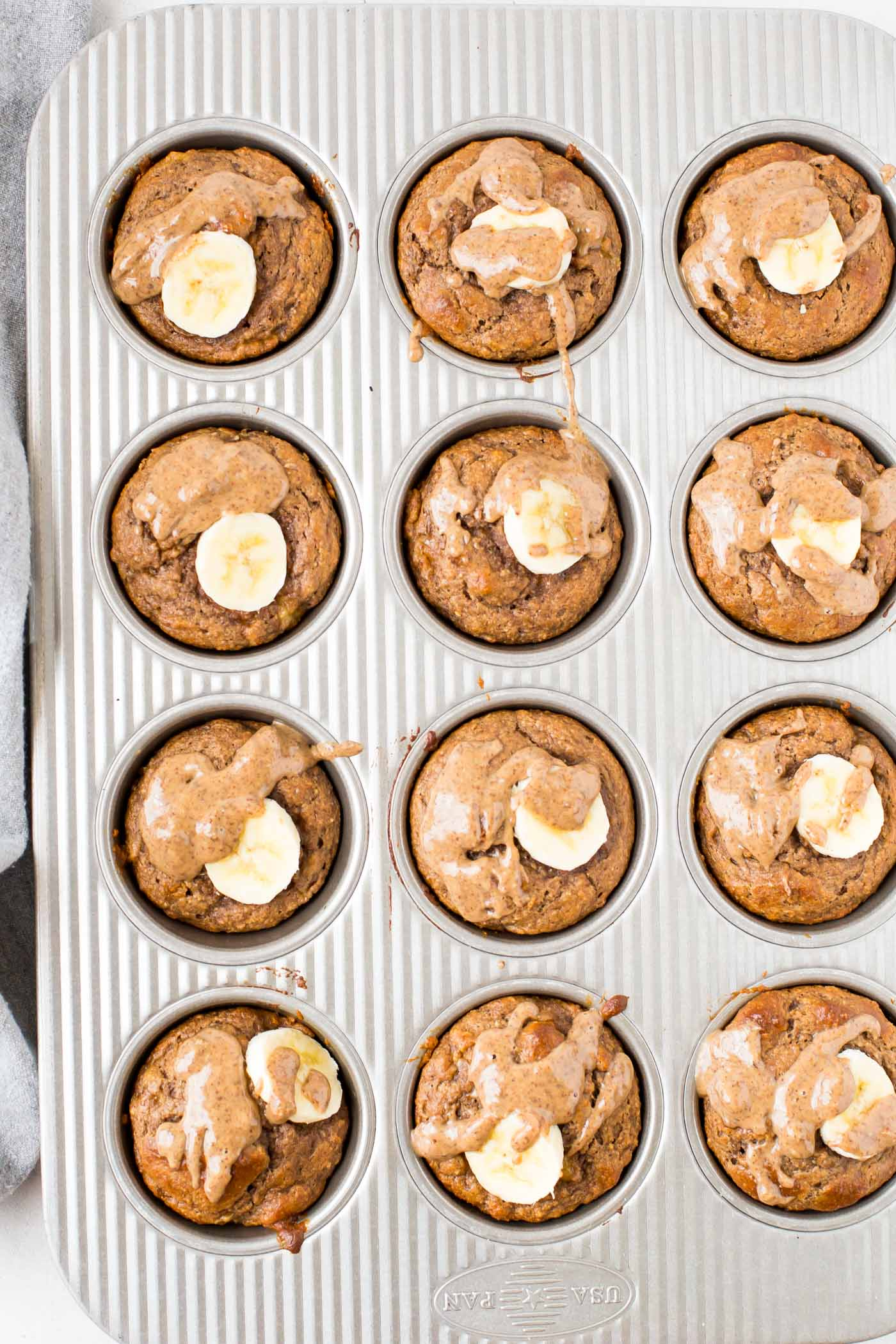 Twelve Banana Protein Powder Muffins in a muffin tin pan