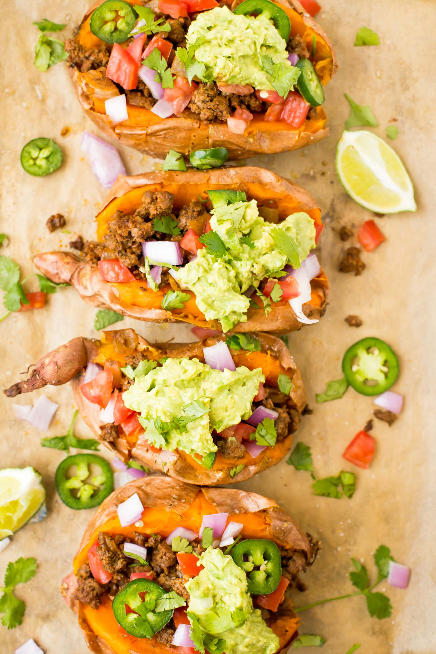 four sweet potatoes stuffed with ground beef, diced jalapenos, onions, and tomatoes, and garnished with cilantro and smashed avocado