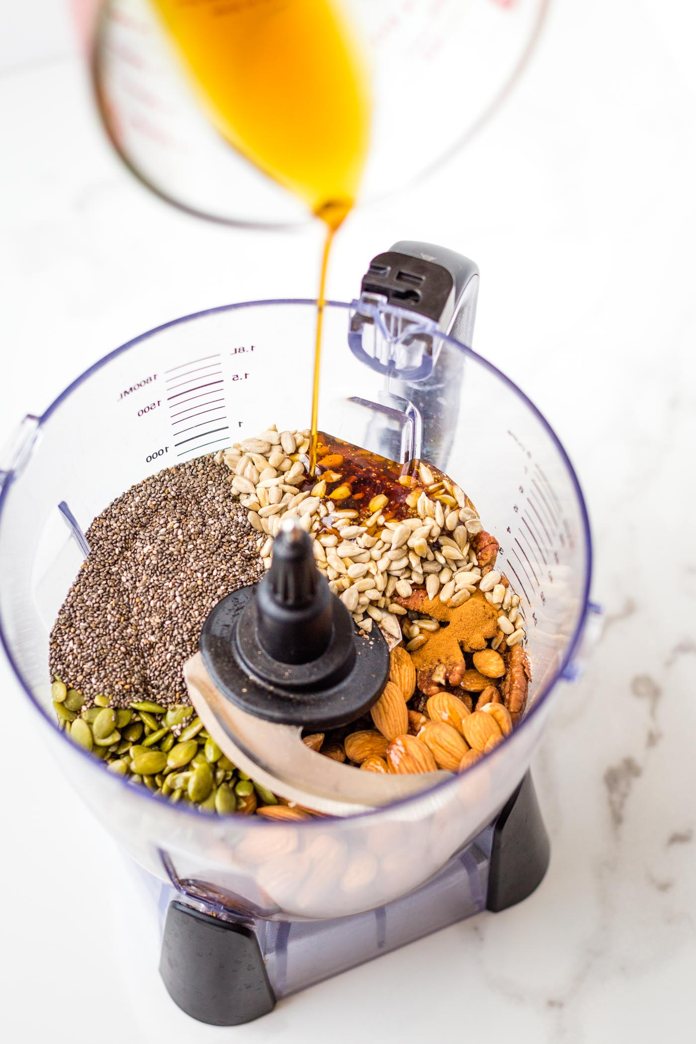 maple syrup being poured over nuts and seeds in food processor