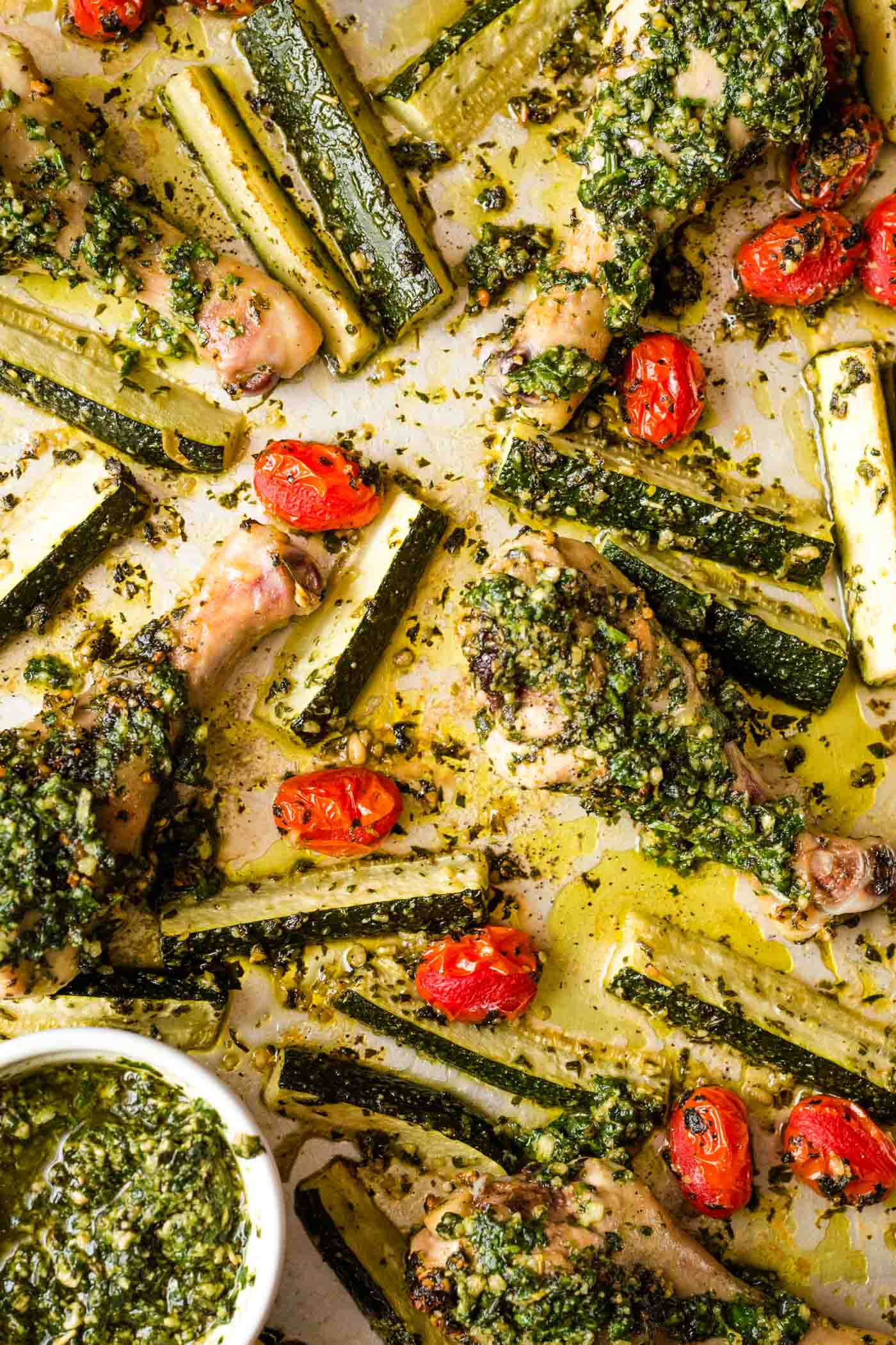 Chicken drumsticks, zucchini, and tomatoes covered in pesto on sheet pan