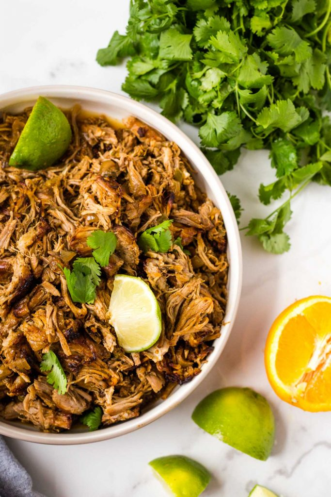 Crispy pork carnitas in bowl with limes, cilantro, and orange