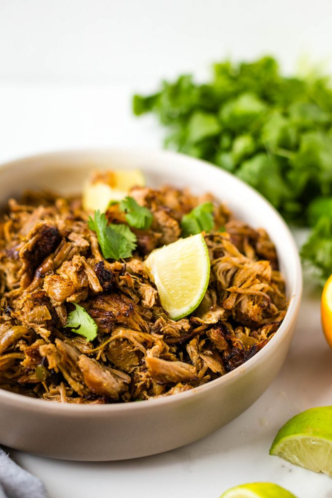 Slow cooker pork carnitas in bowl topped with cilantro and limes