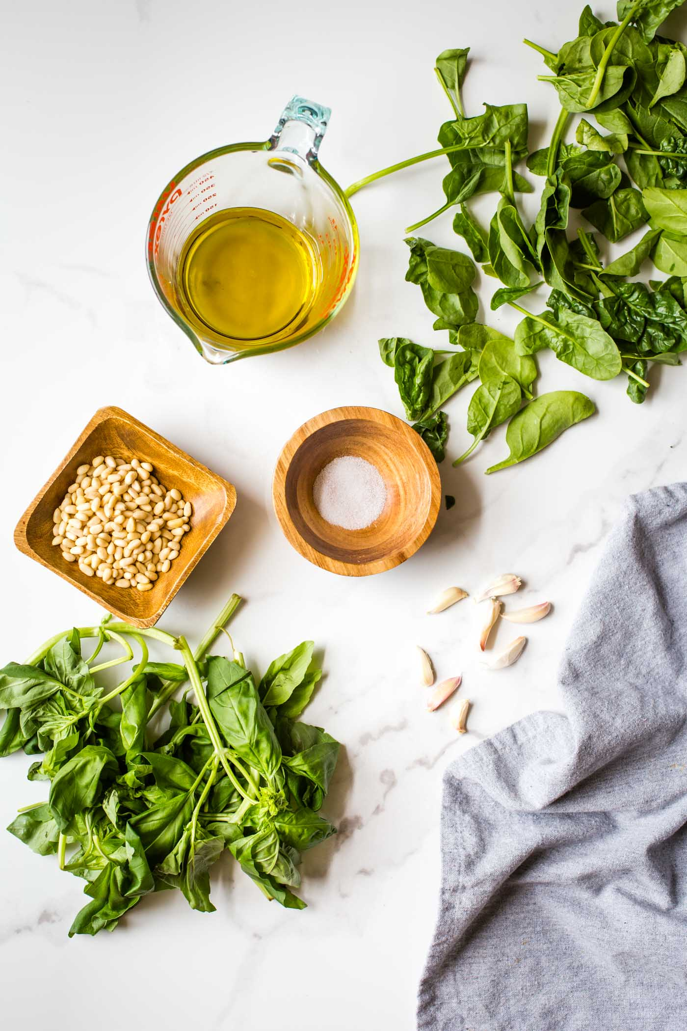 Spinach, basil, olive oil, pine nuts and garlic on white background