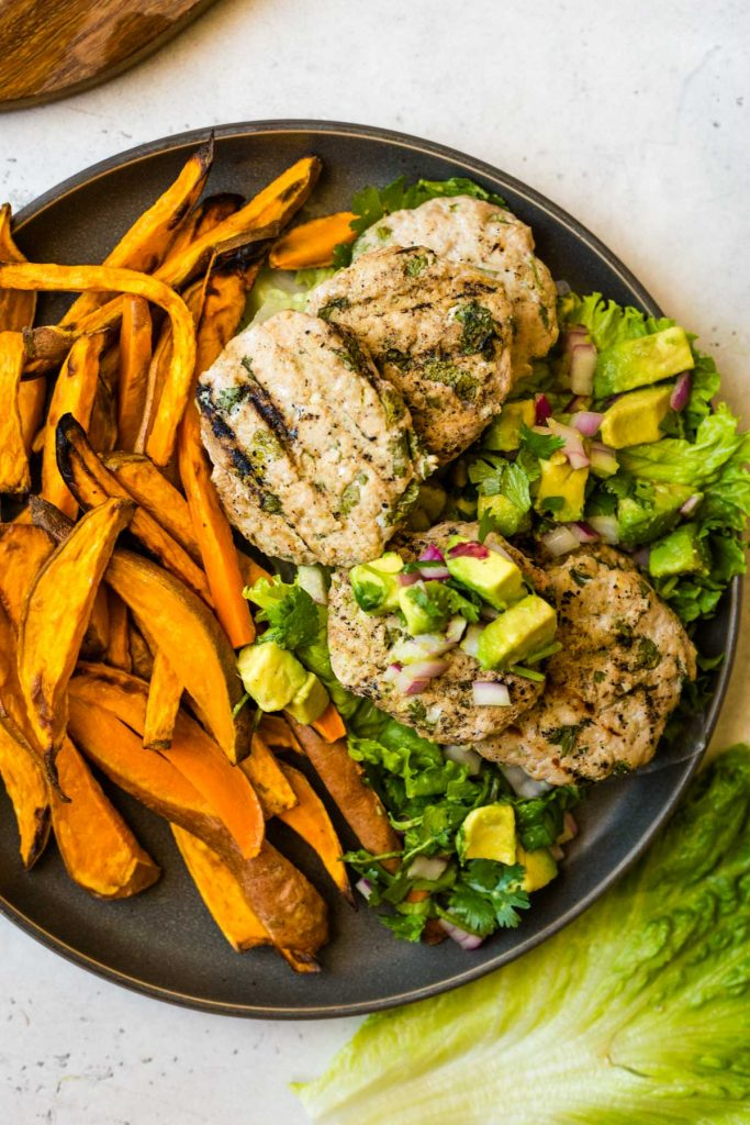 Chicken burger patties, avocado salsa, and sweet potato fries on plate