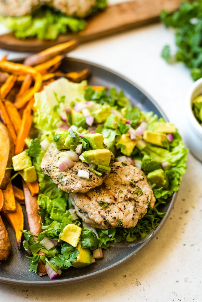 Cilantro Lime Chicken Burgers with avocado salsa on grey plate