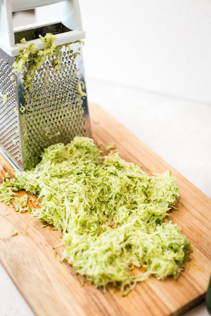 Shredded zucchini on cutting board with grater