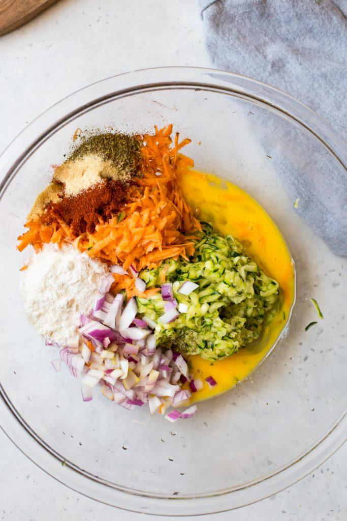 Shredded zucchini, shredded sweet potato, diced onion, whisked egg, and seasonings in glass bowl