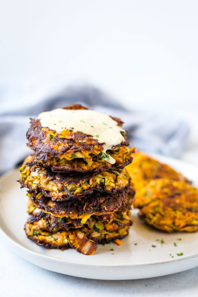 Stacked Zucchini and Sweet Potato Fritters on white plate