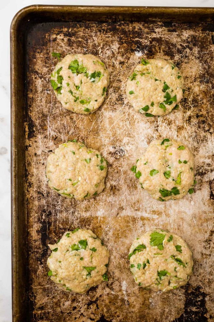 Uncooked cilantro lime chicken burgers on baking sheet
