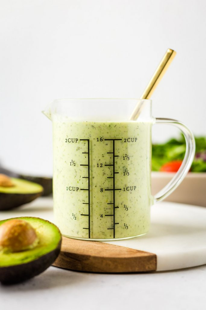 measuring cup filled with avocado ranch dressing