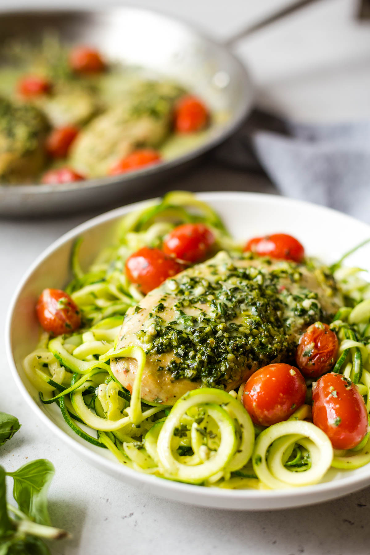 plate with zucchini noodles, tomatoes, and pesto chicken