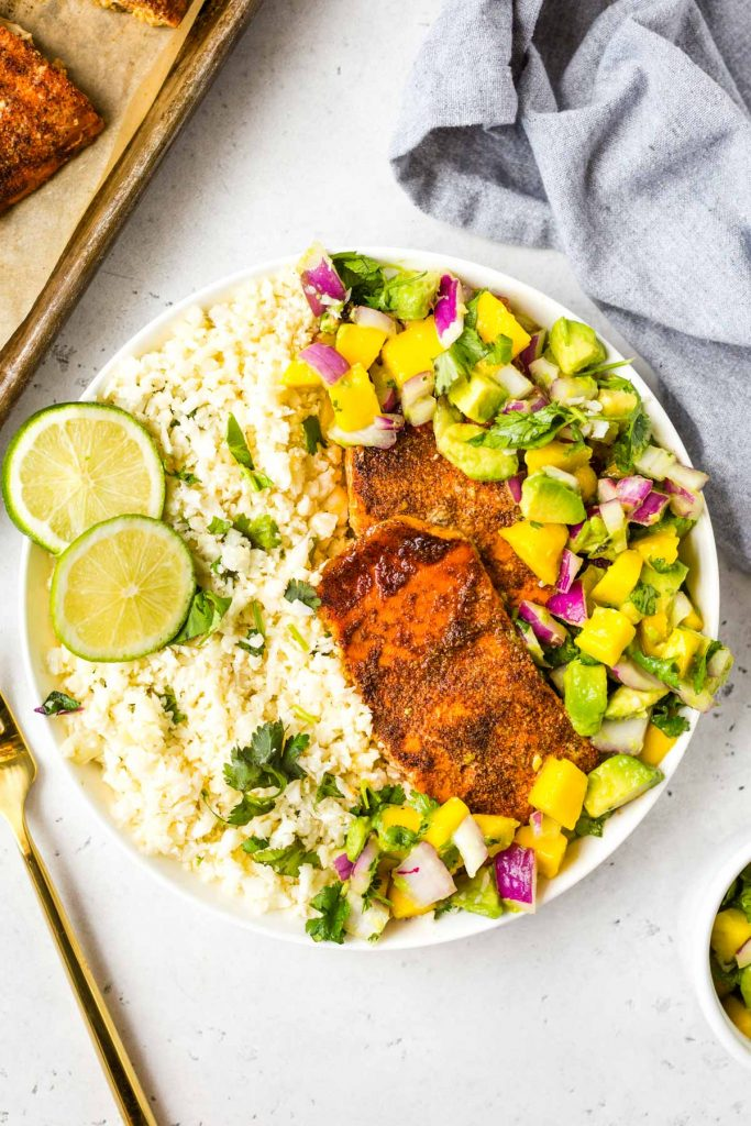 white bowl with cauliflower rice, pieces of salmon, and mango and avocado salsa