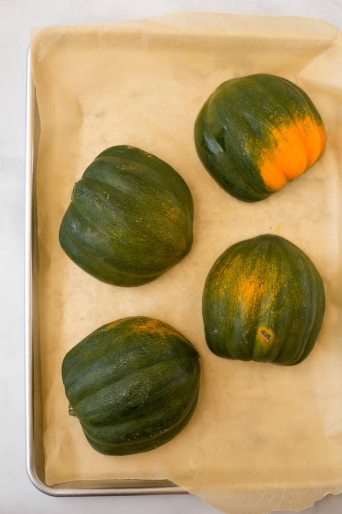 Acorn squash halves face down on baking sheet