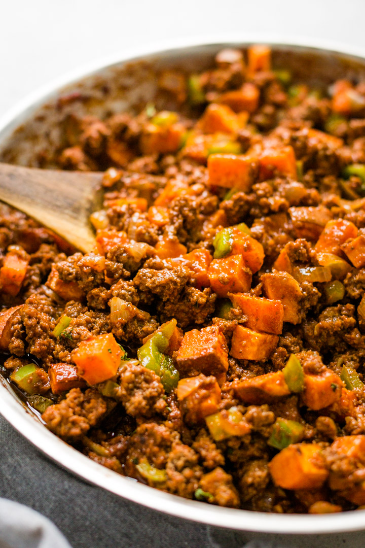 Cubed sweet potatoes and ground beef in skillet