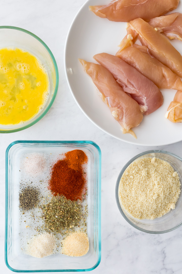 Whisked egg in bowl, raw chicken tenders, seasonings, and almond flour in bowl