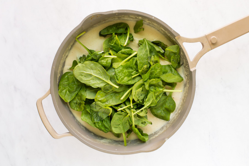 adding spinach to sauce in skillet
